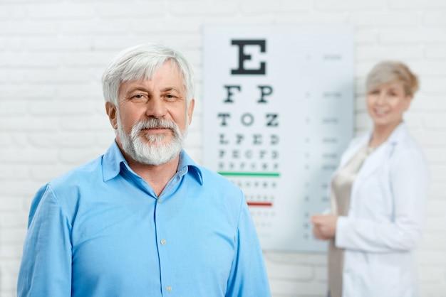 Paciente idoso que fica na frente do oftalmologista.