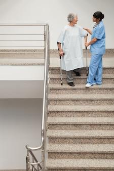 Paciente idoso sendo ajudado pela enfermeira para descer escadas