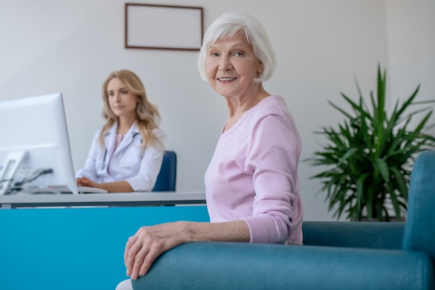 Paciente idoso sorrindo, sentado no consultório médico e parecendo satisfeito
