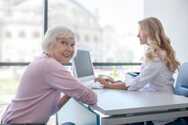 Paciente idoso sorrindo sentado no consultório médico