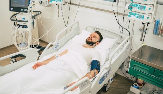 Paciente infectado com coronavírus na enfermaria de quarentena está deitado na cama no hospital.