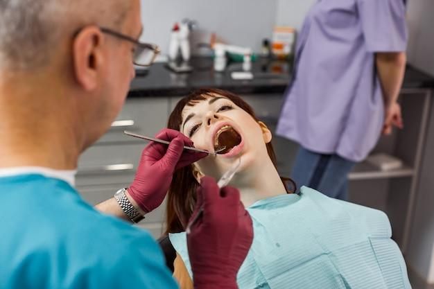 Paciente jovem bonita na clínica odontológica, com verificação e tratamento dentário, mulher com a boca aberta, equipe profissional de dentista, dentista masculino sênior e sua assistente feminina