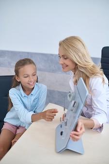 Paciente jovem e fofa, branca, do sexo feminino, escolhendo um aparelho de surdez assistida por uma experiente e simpática otorrinolaringologista