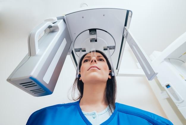 Paciente jovem em pé na máquina de raio-x.
