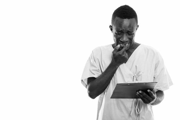 Paciente jovem negro africano lendo na prancheta enquanto parece preocupado e roendo a unha