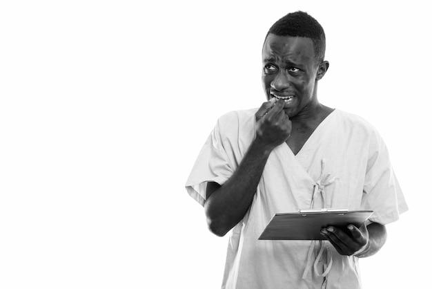 Paciente jovem negro africano pensativo segurando uma prancheta enquanto parece preocupado e roe a unha