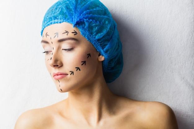 Paciente jovem pacífico com linhas pontilhadas no rosto