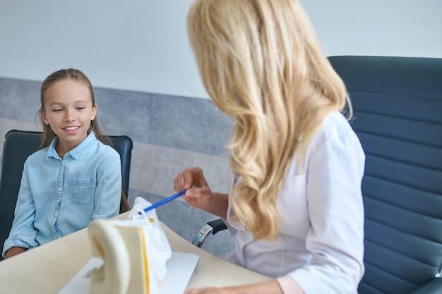 Paciente jovem sendo explicada sobre a anatomia do ouvido humano