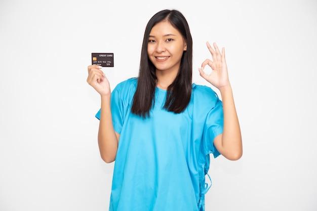 Paciente linda mulher segurando o cartão de crédito de seguro de acidentes pessoais e sinal ok