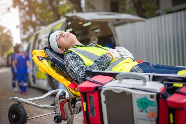 Paciente masculino inconsciente / cabeça quebrada deitado em uma maca de ambulância para transportar feridos para o hospital em uma ambulância.
