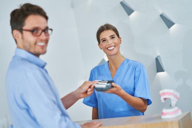 Paciente masculino pagando consulta odontológica na clínica