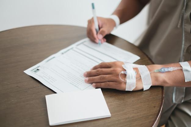 Paciente masculino que assina o formulário do faturamento do tratamento médico e o documento do seguro no hospital.
