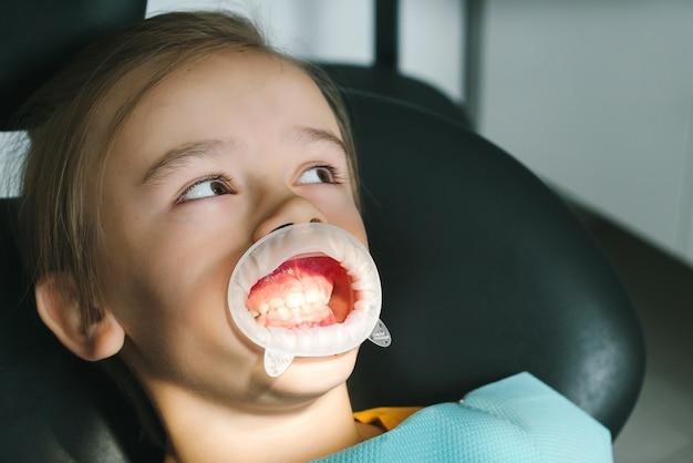 Paciente menino visitante especialista na clínica odontológica. dentista examinando os dentes do menino.