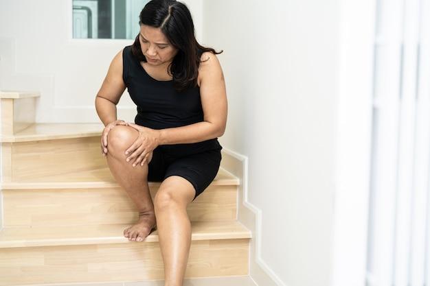 Paciente mulher asiática cai escada abaixo e dor no joelho devido a superfícies escorregadias