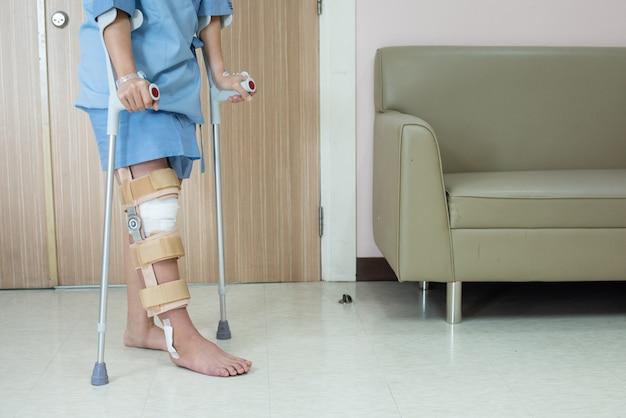 Paciente mulher asiática com cinta de joelho com bengala e suporte de joelheiras na enfermaria do hospital após a cirurgia do ligamento.