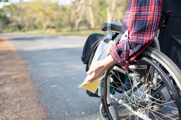 Paciente mulher asiática sentada em uma cadeira de rodas com bolsa de urina no parque