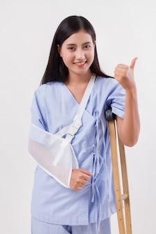 Paciente mulher ferida apontando o polegar para cima, gesto de afastamento