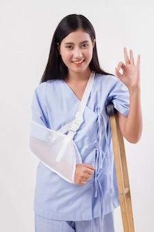 Paciente mulher ferida apontando para cima gesto com a mão ok