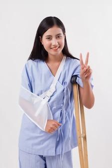 Paciente mulher ferida apontando vitória gesto de 2 dedos