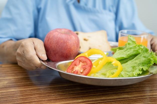 Paciente mulher idosa ou idosa asiática comendo vegetais no café da manhã