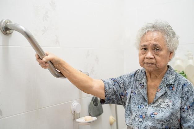 Paciente mulher sênior asiática usar banheiro banheiro lidar com segurança.
