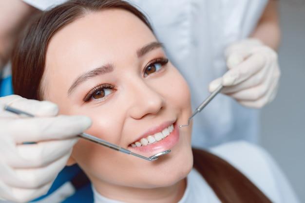 Paciente na cadeira odontológica. mulher jovem e bonita tendo tratamento dentário no consultório do dentista.