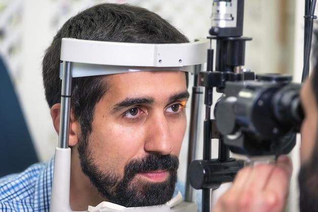 Paciente na clínica moderna da oftalmologia que verifica a visão do olho.