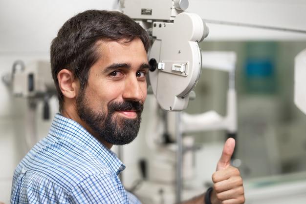 Paciente na clínica moderna de oftalmologia, verificando a visão do olho, aparecendo o polegar.