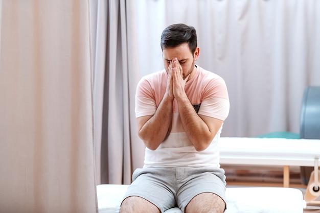 Paciente nervoso, sentado na cama do hospital e orando por bons resultados.