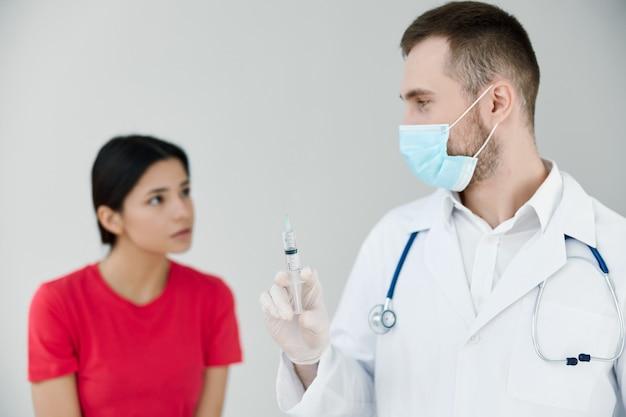 Paciente no hospital olhando para o médico com injeção de seringa na mão. foto de alta qualidade