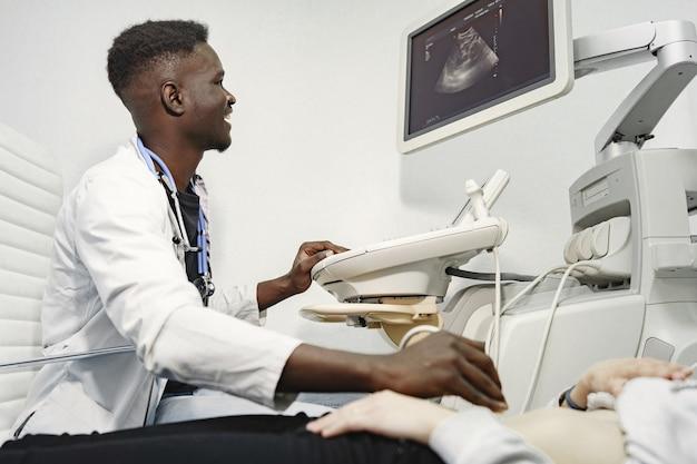 Paciente no sofá. o médico faz um diagnóstico de ultrassom. homem de uniforme branco.
