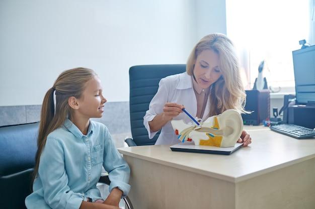 Paciente olhando para o modelo de demonstração do sistema auditivo durante a consulta