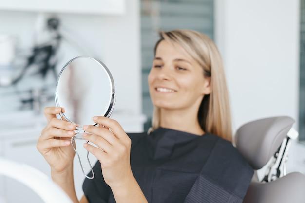 Paciente olhando seu sorriso no espelho após o tratamento.