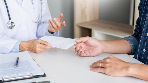 Paciente ouvindo atentamente um médico explicando os sintomas do paciente ou fazendo uma pergunta enquanto discutem a papelada juntos em uma consulta