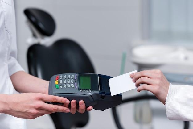 Paciente pagando pelo tratamento odontológico com cartão de crédito