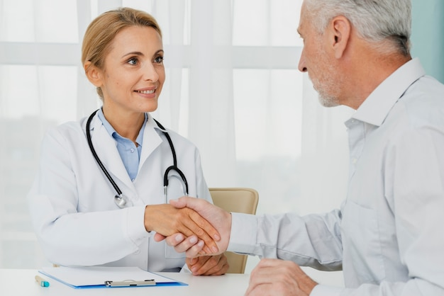 Paciente segurando a mão do médico