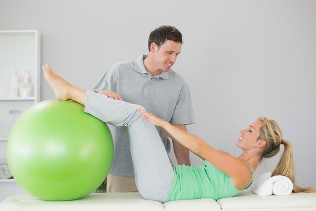 Paciente segurando uma bola de exercício com as pernas