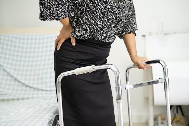 Paciente senhora asiática dor nas costas, pulso ortopédico lombar com andador.