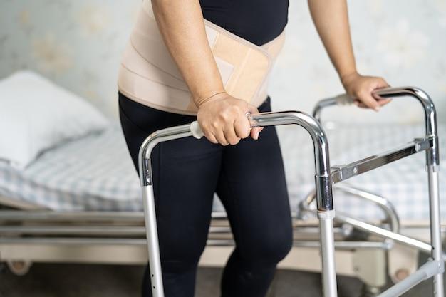Paciente senhora asiática usando cinto de suporte de dor nas costas.