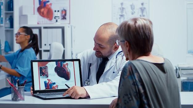 Paciente sênior aposentada em visita ao médico cardiologista. problemas de doença cardíaca apresentados pela cardiologia cardiologista, ligação do coração. cuidados de saúde em clínica privada moderna. diagnóstico da equipe médica