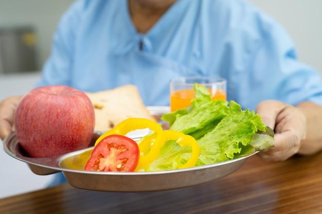 Paciente sênior asiática tomando café da manhã com vegetais saudáveis