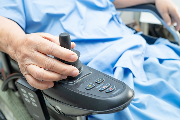 Paciente sênior asiático da mulher na cadeira de rodas elétrica com controle remoto no hospital.
