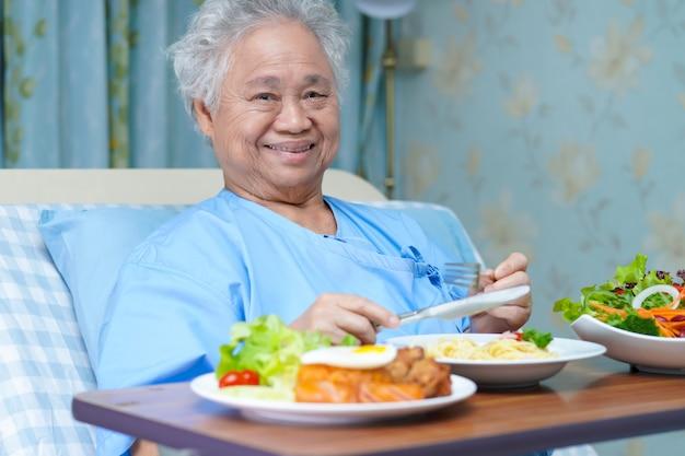 Paciente sênior asiático da mulher que come o café da manhã no hospital.