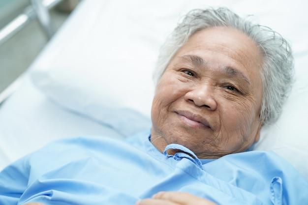 Paciente sênior asiático da mulher que encontra-se para baixo na cama no hospital.