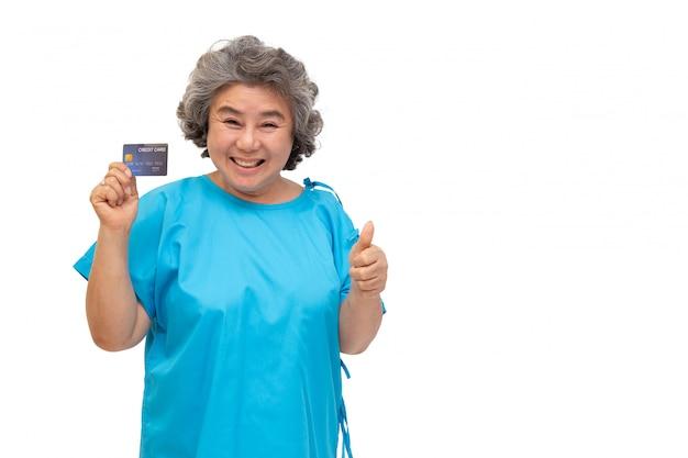Paciente sênior asiático da mulher que mantém o cartão e o polegar de crédito isolados acima no fundo branco.