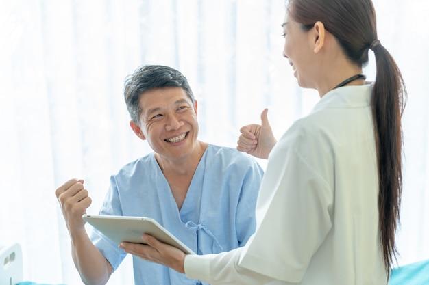 Paciente sênior asiático na cama de hospital discutindo com médico feminino