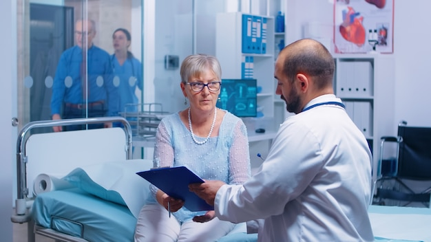 Paciente sênior, assinando o formulário de decisões médicas, sentado na cama do hospital em uma clínica privada moderna. médico com área de transferência, enfermeira trabalhando em backgorund. documentos do sistema médico-medicinal de saúde contra