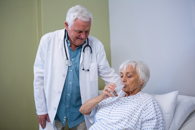 Paciente sênior bebendo um copo d'água