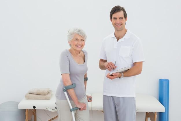 Paciente sênior de terapeutas e deficientes com relatórios