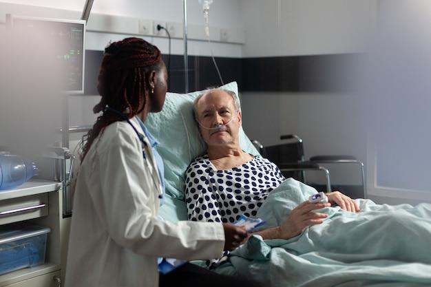 Paciente sênior doente, deitada na cama, respirando por meio de tubo de ensaio de oxigênio, ouvindo o médico